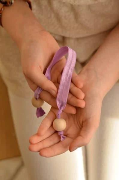 Thắt nút một đầu dây chun sau khi đã xỏ qua hạt gỗ và thao tác tương tự với đầu dây chun bên còn lại (Nguồn: Internet)