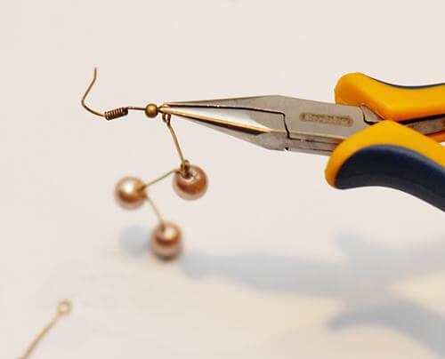 Mở rộng phần khoen tròn của khuyên móc và móc nó vào phần khoen tròn có chứa hạt cườm rồi dùng kìm đóng lại (Nguồn: Internet)